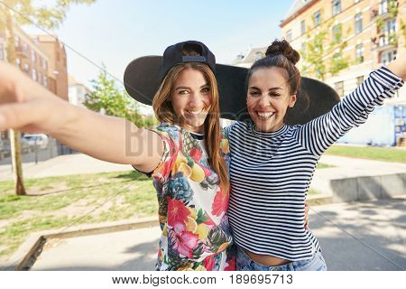 Two Trendy Young Skateboarders Posing Arm In Arm