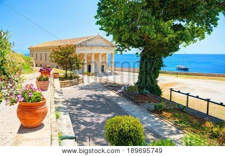 View on classical Greek temple Saint George church architecture of Greece Corfu island capital Kerkyra. Classic yacht. Greece holidays vacation touristic tours. Old Venetian Fortress sightseeing tour