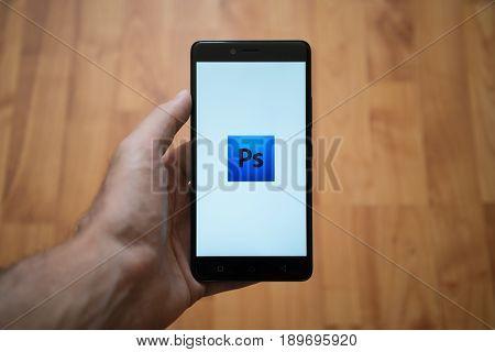 London, United Kingdom, june 5, 2017: Man holding smartphone with Adobe photoshop logo on the screen. Laminate wood background.