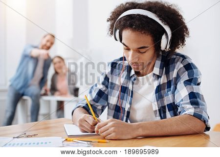 Study hard. Handsome committed intelligent guy sitting at the table and writing something down while wearing the headphones