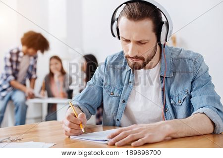 Isolated from environment. Focused nice creative guy working on his assignment while listening to music which helping him concentrating