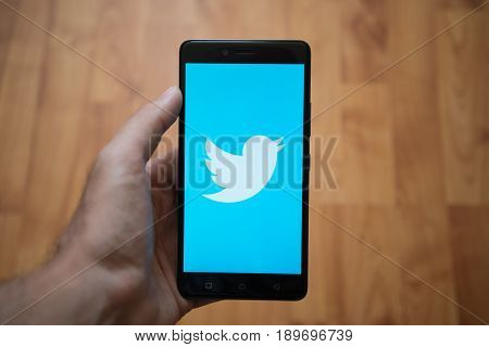 London, United Kingdom, june 5, 2017: Man holding smartphone with Twitter LOGO on the screen. Laminate wood background.