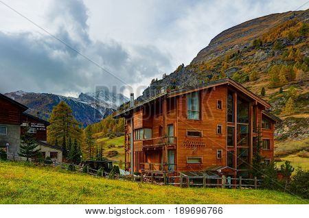 ZERMATT, SWITZERLAND, OCT,20, 2010: View on Swiss cottage chalet style wooden architecture hotels in luxury Swiss cottage style and Matterhorn mountain peak. swiss ski bike holidays vacations tours