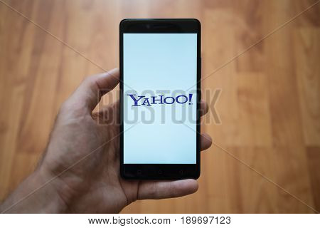 London, United Kingdom, june 5, 2017: Man holding smartphone with Yahoo LOGO on the screen. Laminate wood background.