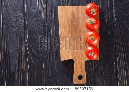 four raw fresh red ripe tomatoes on brown plate
