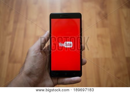 London, United Kingdom, june 5, 2017: Man holding smartphone with Youtube LOGO on the screen. Laminate wood background.