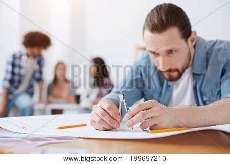 Completing drawing. Young responsible inventive man sitting in class and working on the project he needing submitting at the end of the semester