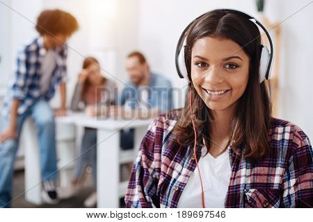 Perfect playlist for work. Lively enchanting talented woman listening to her favorite music while sitting in class and studying her subject