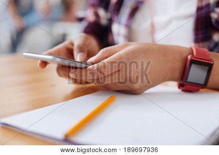 Online communities. Charismatic outgoing cheerful woman holding her smartphone and typing a new message while communicating with fellow students