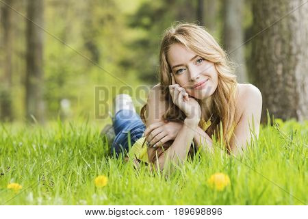 Pretty woman lying down on dandelions field happy cheerful girl resting on dandelions meadow, relaxation outdoor in springtime, vacation