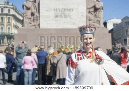 Latvia Riga-may 4.2017: Portrait of a girl in a Latvian national costume against the background of the Freedom Monument in Riga on the Day of Restoration of Independence of Latvia