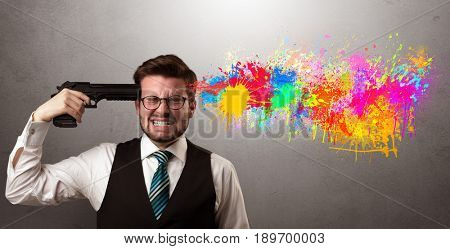 Man shoots his head with gun and colorful splotch are coming out from his head