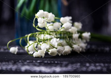 Lily of the valley on wooden background. Lily of the valley bouquet