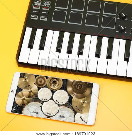 Musical instrument - MIDI keyboard and Drum kit on the smartphone screen for the composition of music. On a yellow background.