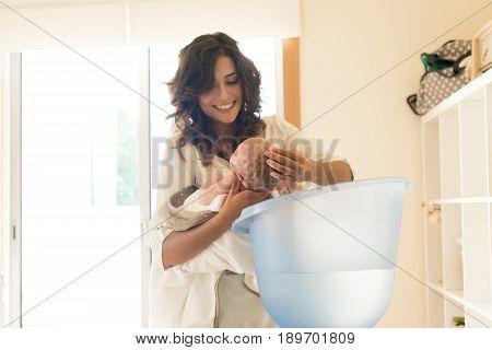 Mother Washing Baby In Bath Tub