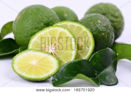 A close up of whole and slices of Kaffir lime with leaves.  Used in asian cuisine and have strong citrus fragrance.  Also known as Limau Purut in Malaysia.  White background.