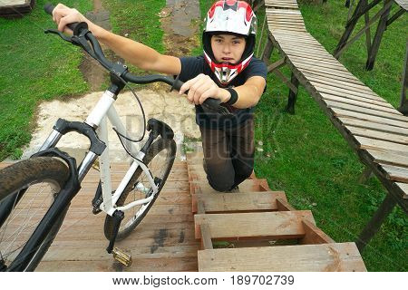 young boy go up to the ramp with his BMX Bike at the skate park.