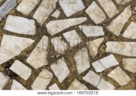 Old weathered stone tiles. Remains antique abandoned terrace. Fragments, pieces, flinders, debris, details, decor. Broken marble texture for design, templates, backgrounds, textures, prints, work.