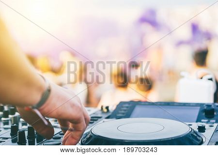 Close up of DJ's hand playing music at turntable on a beach party festival - Portrait of DJ mixer audio in a beach club above the crowd dacing and having fun - Party summer music and people concept
