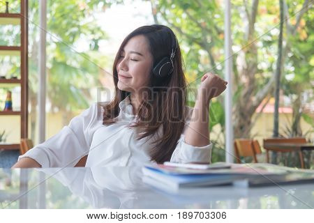 A beautiful asian woman close her eyes and enjoy listening to music with headphone in cafe with feeling relax and green nature background