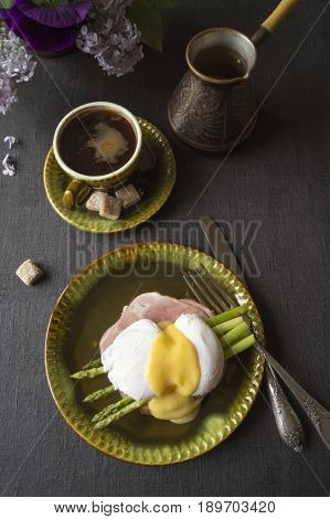 Breakfast. Eggs Benedict with asparagus and coffee.