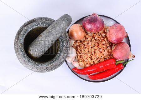 Dried shrimp, fresh red chilies, Bombay onions, shallots, fresh garlic, on a white ceramic plate with blue outer ring line.  Pestle and mortar on a white background.