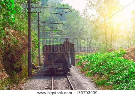 Worker stands on the tail of empty freight train. Yuejin. Jiayang Mining Region. Sichuan province. China