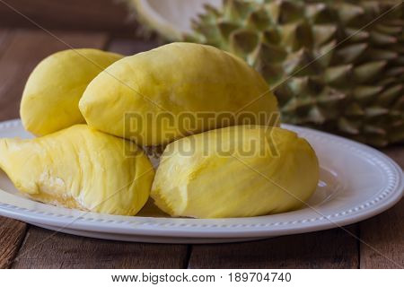 Traditional Thai fruit :Durian is the king of fruit in Thailand. Durian on white plate put on rustic wood table. Durian is tropical fruit so delicious sweet and good smell. Ripe durian has yellow gold color. Delicious Durian on white plate.