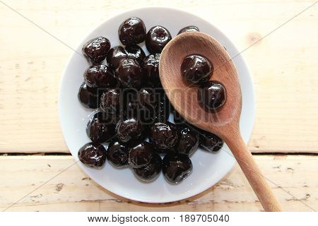 Amarena cherries on a white plate with a wooden spoon