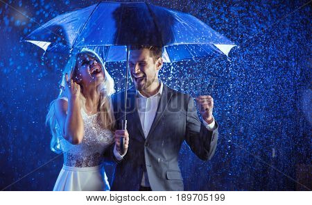 Attractive couple under umbrella walking at night