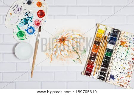 Hand Drawn Bright Sketch of Orange Lily Flower, with lying paints, paintbrushes and palette on the white brick background - concept of human creativity, top flat view