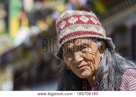 HIMALAYAS ANNAPURNA REGION NEPAL - OCTOBER 15 2016 : Unidentified old Nepalese woman with wrinkled face portrayed in a Himalayan village in Nepal