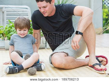 Young man with son playing with little hedgehog baby