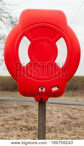 Bright Red Lifebuoy Case On Wooden Pole