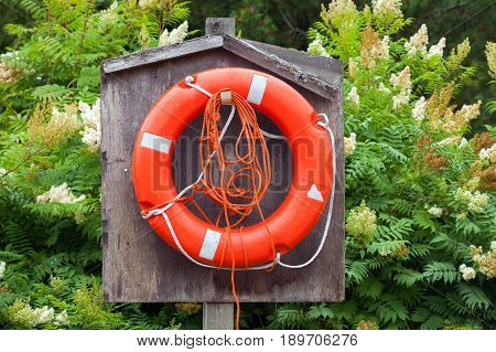 Red Lifebuoy With Ropes Hanging In Wooden Box