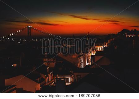 View from hight point of illuminated narrow street with beautiful old facades of residential houses following to rope bridge during stunning red and orange sunset in Lisbon Portugal
