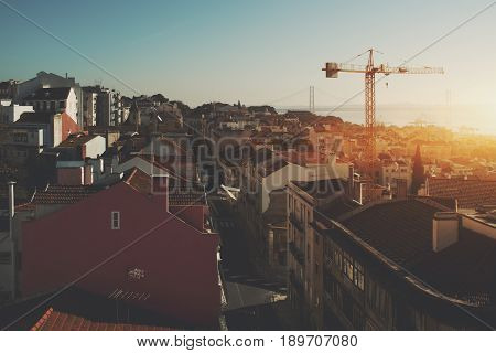 View of morning sunny narrow street in central district of Lisbon in Portugal with teal sky small ancient houses with beautiful facades construction cranes huge famous rope bridge and hazy horizon
