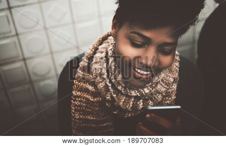Cheerful afro american girl sitting on the bench of metro near wall and having chat via smartphone happy black curly young female using her mobile telephone while sitting in front of patterned wall