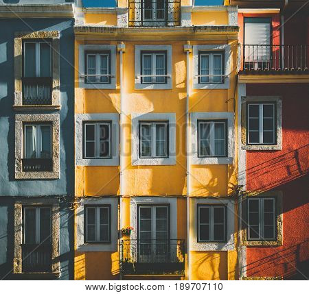 Multicolored facade of old traditional residential building in Lisbon view of colorful frontage of living house in Portugal with multiple windows and balconies on bright sunny day