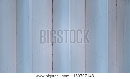 Striped texture of folding door of garage or street shop's facade with vertical lines in joints on white metal multiple seams uniform cold lighting