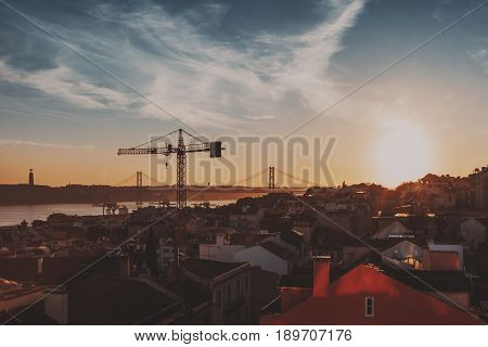 View of central district of Lisbon in Portugal on sunny evening with teal sky small ancient houses with beautiful facades construction cranes huge famous rope bridge and Jesus monument in distance
