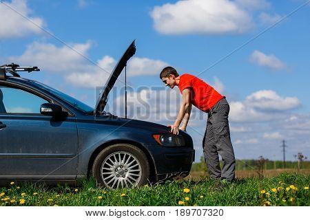 Brunet looks into open hood of car