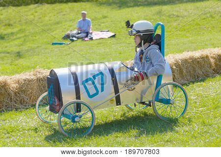 STOCKHOLM SWEDEN - MAY 21 2017: Boy driving a home made soapbox car downhill on a field in the race Gardesloppet at Djurgarden Stockholm Sweden. May 21 2017