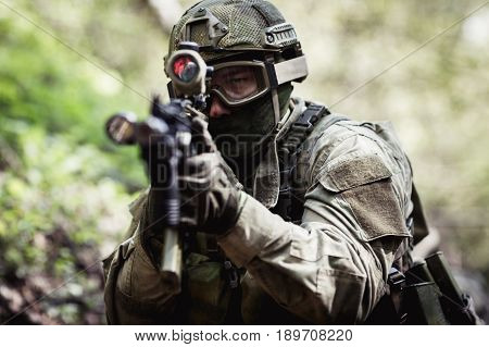 Photo of sighted sniper in woods during day