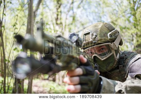 Portrait of soldier with submachine gun in woods afternoon