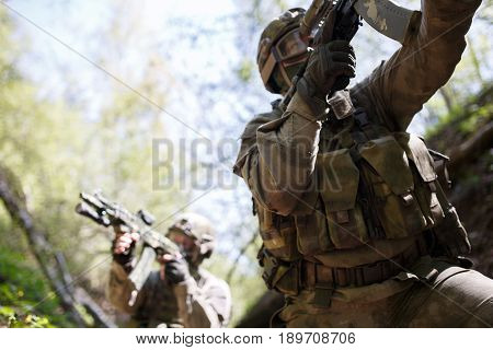 Soldiers with submachine gun in war at woods
