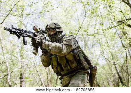 Military man with submachine gun in forest on reconnaissance