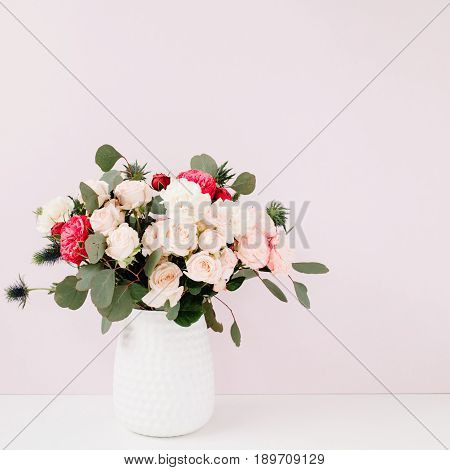 Beautiful flowers bouquet in flowerpot in front of pale pastel pink wall. Floral lifestyle composition.
