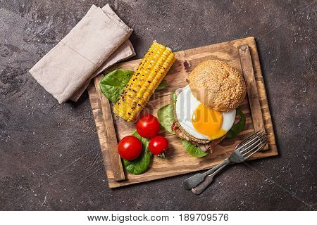 Homemmade Bacon Hamburger with fried Egg, Lettuce and lentil burger with a garnish of corn and tomatoes, top view