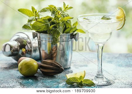 Fresh classic lime margarita cocktail in margarita glass with ice and mint
